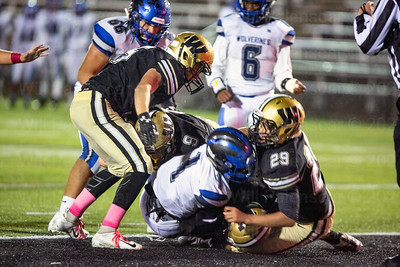 Aron Dishun #9, Gavin Kiley #5 , Caleb Wheatland #29 assist a teammate who sacked the    West Potomac's Deandre Doherty #1 for a safety.