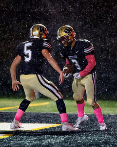 Gavin Kiley #5 and Saadiq Hinton #3 celebrate in the end zone after a touchdown and during heavy rains.