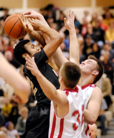 Winchester's Kiante Enis gets his shot blocked by Frankton's Jordan Reeves as teammate Nick Wright helps with the defensive pressure.