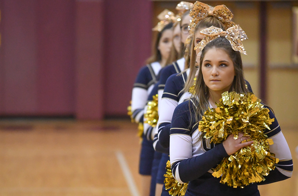 . Eric Bonzar�The Morning Journal Olmsted Falls Bulldogs cheerleaders place their hands over their hearts as the Avon Lake band plays the The Star Spangled Banner,  Jan. 13, 2017.