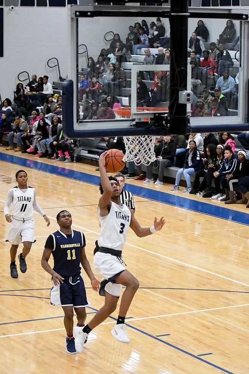 . Eric Bonzar�The Morning Journal<br> Lorain guard Devone Grant (3) gets by Warrensville Heights defender Anthony Wright (11) for the layup.