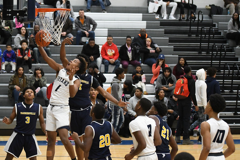. Eric Bonzar�The Morning Journal<br> Lorain forward Jordan Jackson (1) is fouled on his way to the rim by Warrensville Heights\' Shawn Dunnings (1).