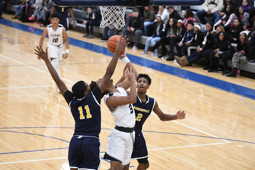 . Eric Bonzar�The Morning Journal<br> Lorain\'s Devone Grant (3) is fouled on the way to the basket by Warrensville Heights\' Anthony Wright (11).