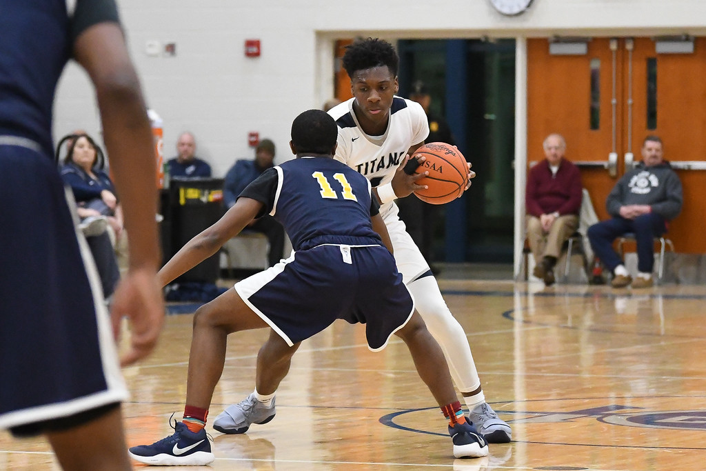 . Eric Bonzar�The Morning Journal<br> Lorain foward Taevon Pierre-Louis moves the ball beyond half court past Warrensville Heights defender Anthony Wright (11).