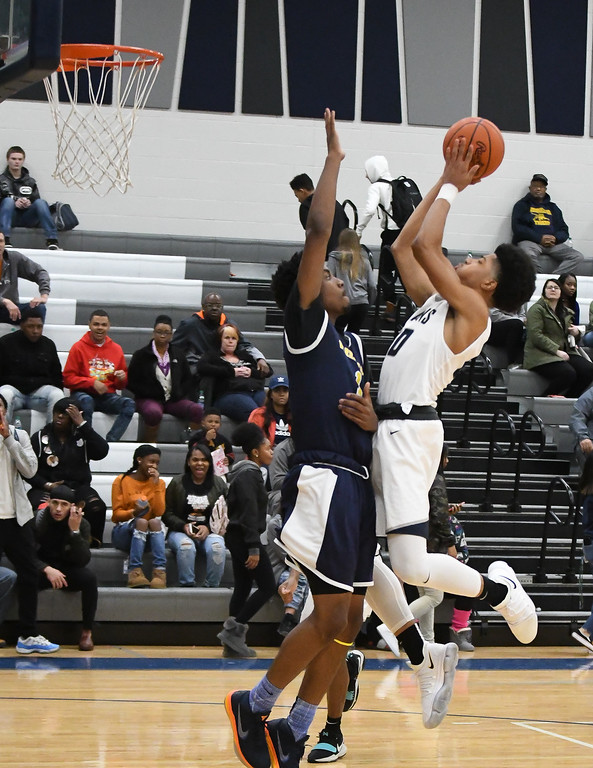 . Eric Bonzar�The Morning Journal<br> Lorain forward Levell Hall (10) shoots over Warrensville Heights\' Shawn Dunnings (1).