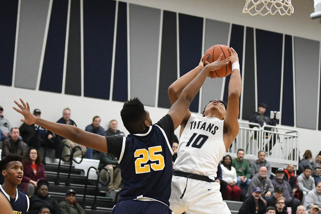 . Eric Bonzar�The Morning Journal Lorain forward Levell Hall (10) goes to the rim as he\'s defended by Warrensville Heights\' Jamal Brown (25).