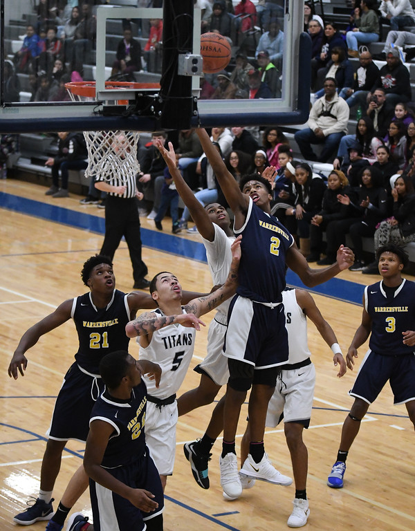 . Eric Bonzar�The Morning Journal<br> Warrensville Heights\' Brandon Rush (2) and Lorain guard Jodeci Crite go up and battle for a rebound under the rim.
