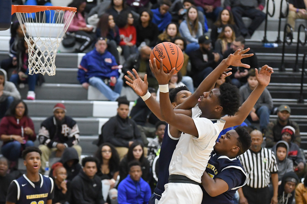. Eric Bonzar �The Morning Journal Lorain sophomore Taevon Pierre-Louis is fouled by Warrensville Heights\' DaQuan Henderson, left, as he drives to the rim, Feb. 10, 2017.