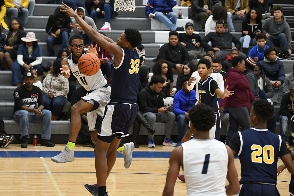 . Eric Bonzar �The Morning Journal Lorain\'s Marqua Black-Wright (11) passes under the hoop to teammate Octavious Wilson (1), Feb. 10, 2017.