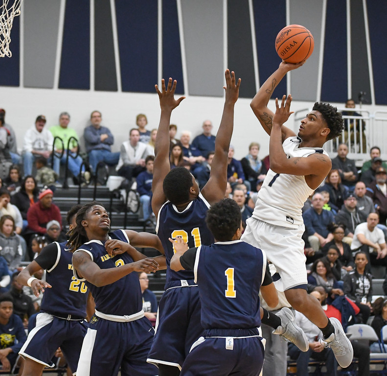. Eric Bonzar �The Morning Journal Lorain\'s Octavious Wilson (1) shoots a one-handed jumper over the defense of Warrensville Heights\' Javon Johnson (21), Feb. 10, 2017. Wilson had a game-tying high 22 points in the Titans\' 82-47 win over the Tigers.