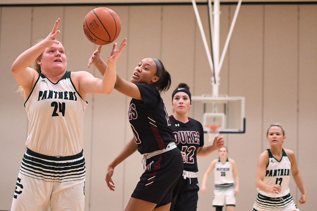 . Eric Bonzar�The Morning Journal<br> Elyria Catholic\'s Abby Winnen (24) and Wellington\'s Jalen Gibbs (10) fight for a loose ball.