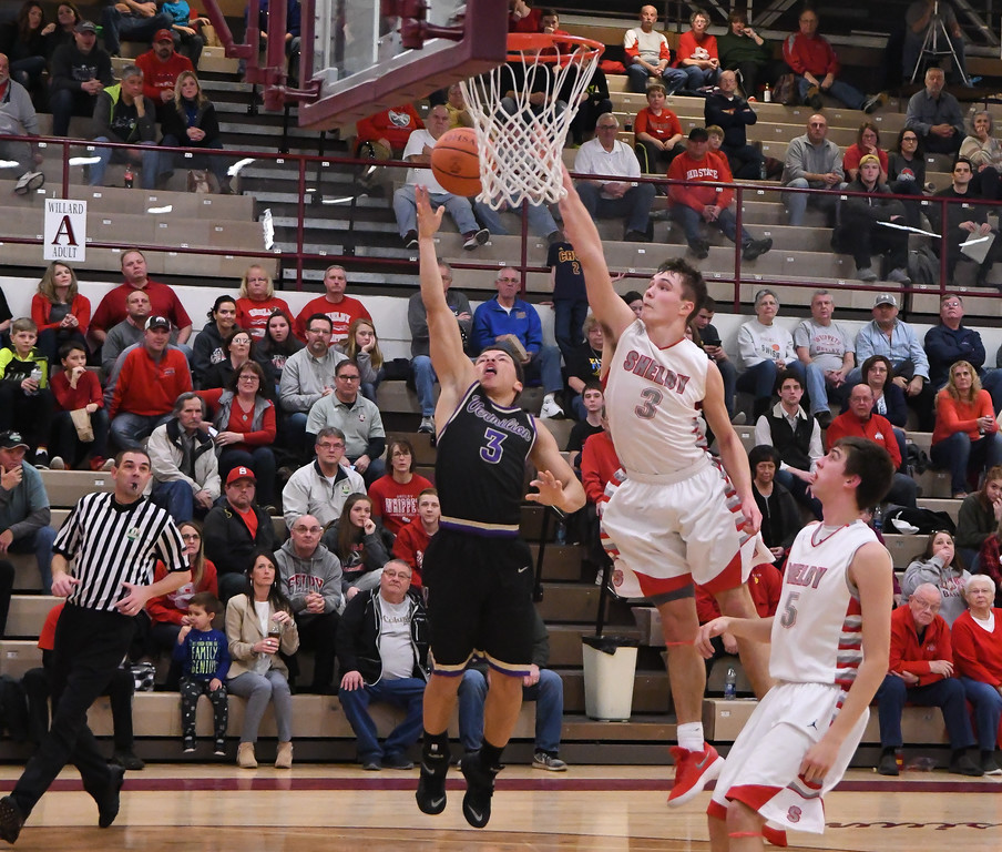 . Eric Bonzar�The Morning Journal<br> Vermilion\'s Eli Balek gets by Shelby guard Uriah Schwemley for an and-one, March 2, 2018.
