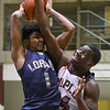 Eric Bonzar—The Morning Journal<br /> Lorain's Octavious Wilson (1) is fouled under the basket by Maple Heights' Daray Menefield (24), Feb. 3, 2017.