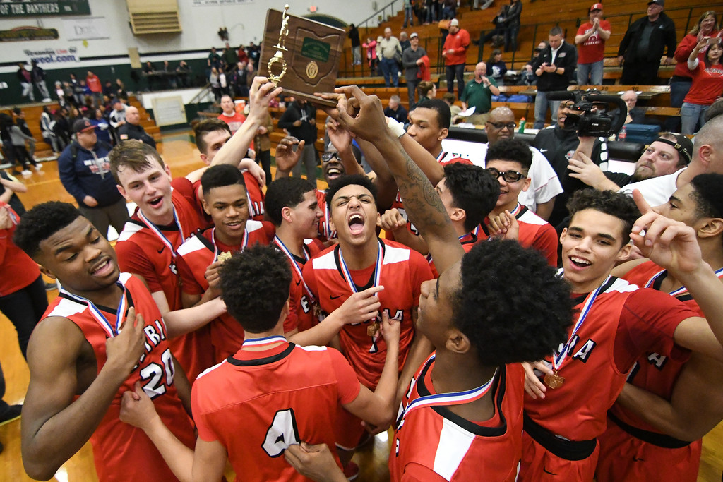 . Eric Bonzar�The Morning Journal The Elyria Pioneers hoist the OHSAA D-I District Championship trophy after knocking off the top-seeded Lorain Titans, 55-47, March 11, 2017.