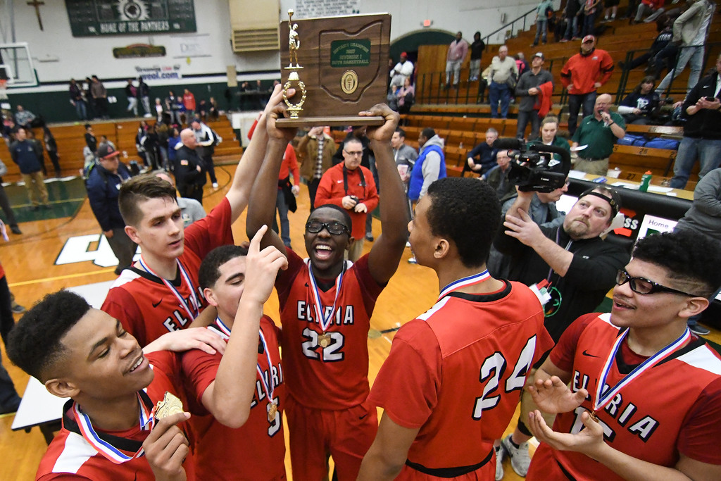 . Eric Bonzar�The Morning Journal Elyria senior Antonio Blanton (22) holds up his team\'s OHSAA D-I District Championship trophy after knocking off top-seeded Lorain, 55-47, March 11, 2017.