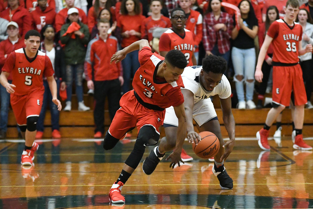 . Eric Bonzar�The Morning Journal Elyria guard Michael Oliver and Lorain sophomore Taevon Pierre-Louis fight for a loose ball at mid-court, March 11, 2017.