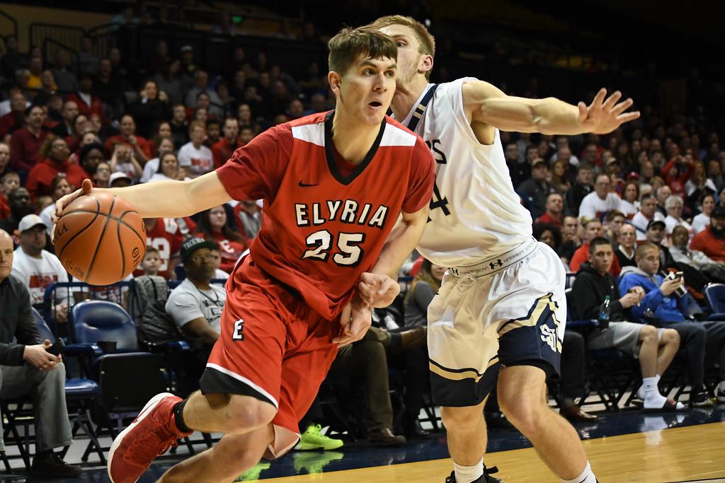 . Eric Bonzar�The Morning Journal Elyria\'s Josh Lotko (25) drives baseline past St. John\'s forward Joe Fretti (24), March 15, 2017.