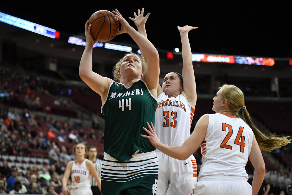 . Eric Bonzar�The Morning Journal<br> Elyria Catholic sophomore Ally Winnen (44) goes vertical to the rim as she\'s defended by Versailles Tigers\' Kelsey Custenborder (33), March 15, 2018.