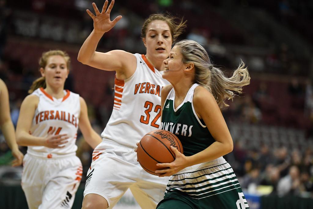 . Eric Bonzar�The Morning Journal<br> Elyria Catholic junior guard Faith Williams cuts to the basket past Versailles Tigers forward Danielle Winner, March 15, 2018.