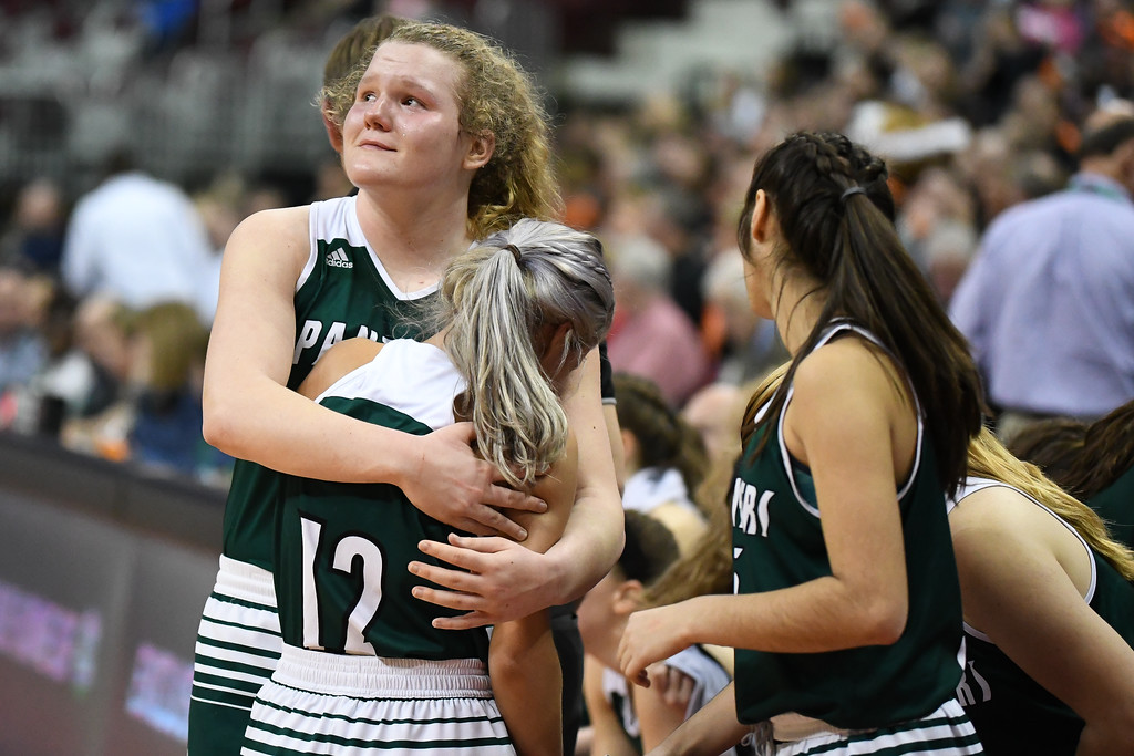 . Eric Bonzar�The Morning Journal<br> Elyria Catholic sophomore Ally Winnen hugs junior guard Faith Williams as the last seconds tick off the clock in the Panthers\' 63-47 loss to the Versailles Tigers, March 15, 2018.