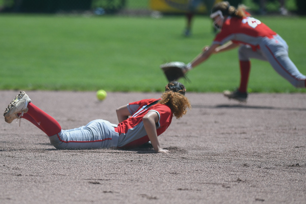 . Eric Bonzar�The Morning Journal<br> A hit gets through the gap past Elyria\'s Kerrigan Williams (17) and April Howser.