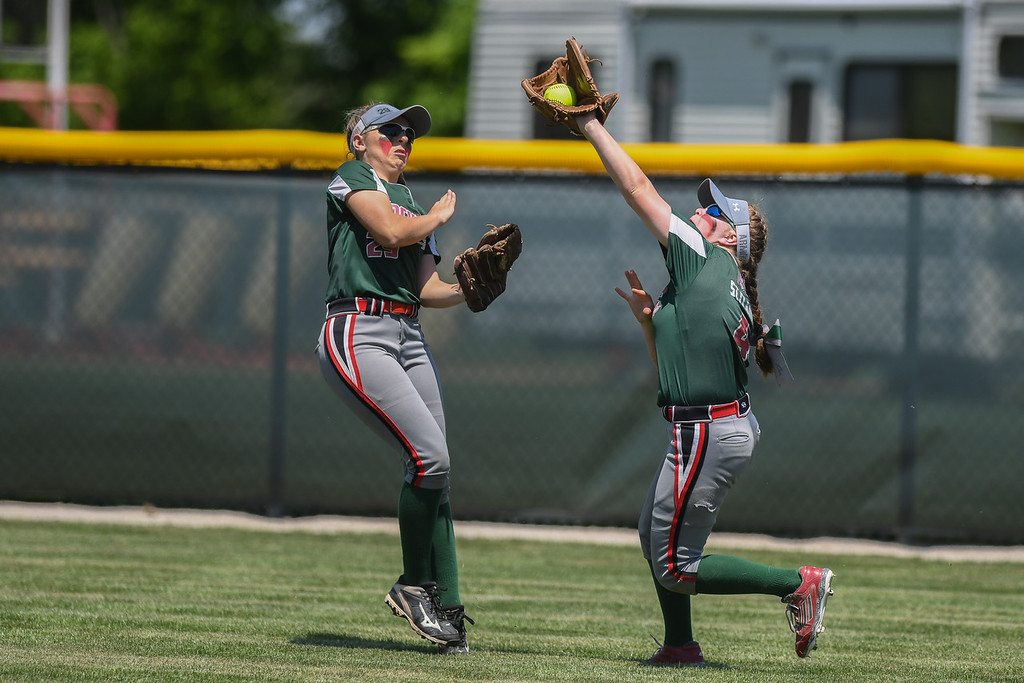 . Eric Bonzar�The Morning Journal<br> Oak Harbor\'s Lauren St. Clair (4) tracks a fly ball as teammate Seree Petersen backs off the play.