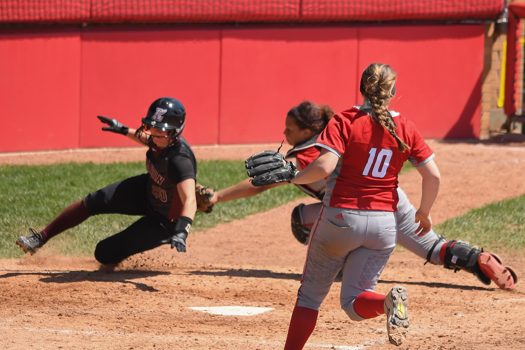 . Eric Bonzar�The Morning Journal Elyria\'s Riley Zana (10) moves to back up catcher Maycee Godbolt as she tags Lebanon\'s Madison Degennaro out at home plate.