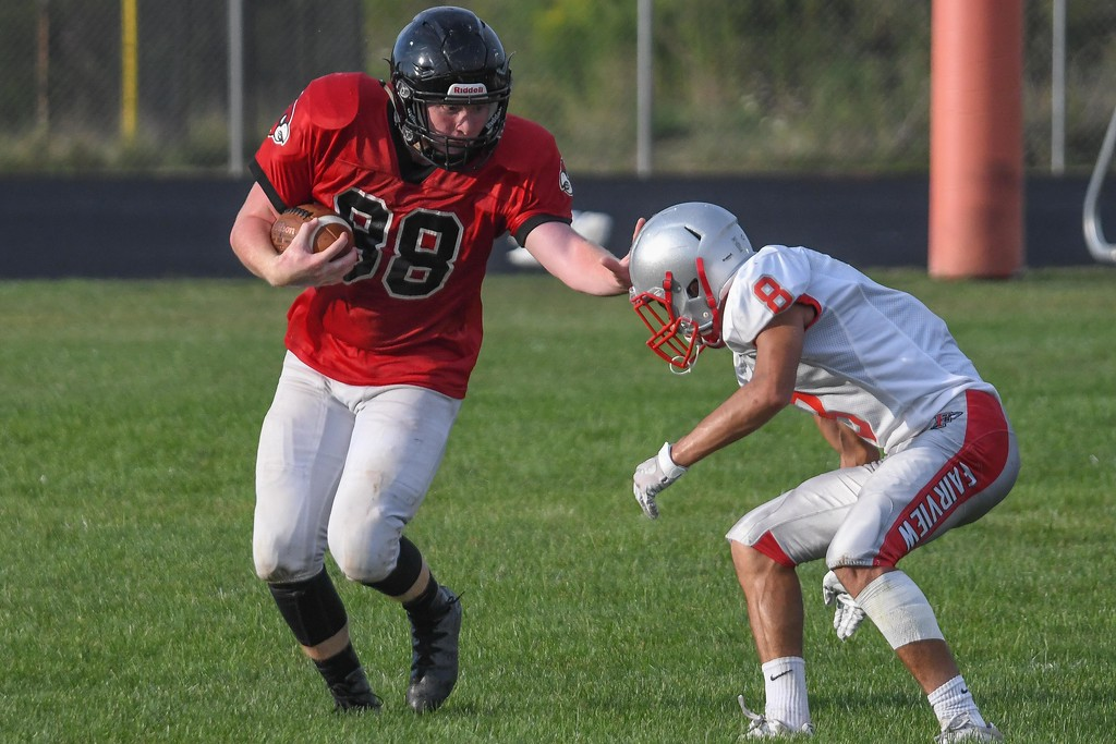. Eric Bonzar�The Morning Journal Brookside\'s Nate Brown (88) stiff arms his way past Fairview\'s Turner Hahn (8).