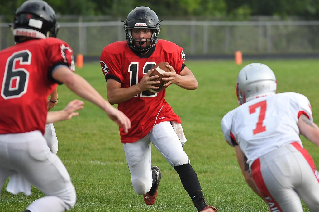 . Eric Bonzar�The Morning Journal Brookside quarterback Jonathan Hice (12) looks for a gap as he scrambles up the middle.