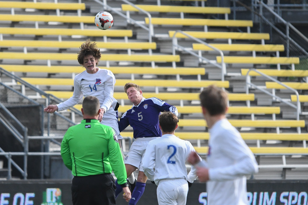 . Eric Bonzar�The Morning Journal<br> Bay forward Cade Gergye (14) clears the ball with a header over Columbus St. Francis DeSales\' defensive forward Alex Whalen (5) in the D-II State Soccer Championship game, Nov. 11, 2017.