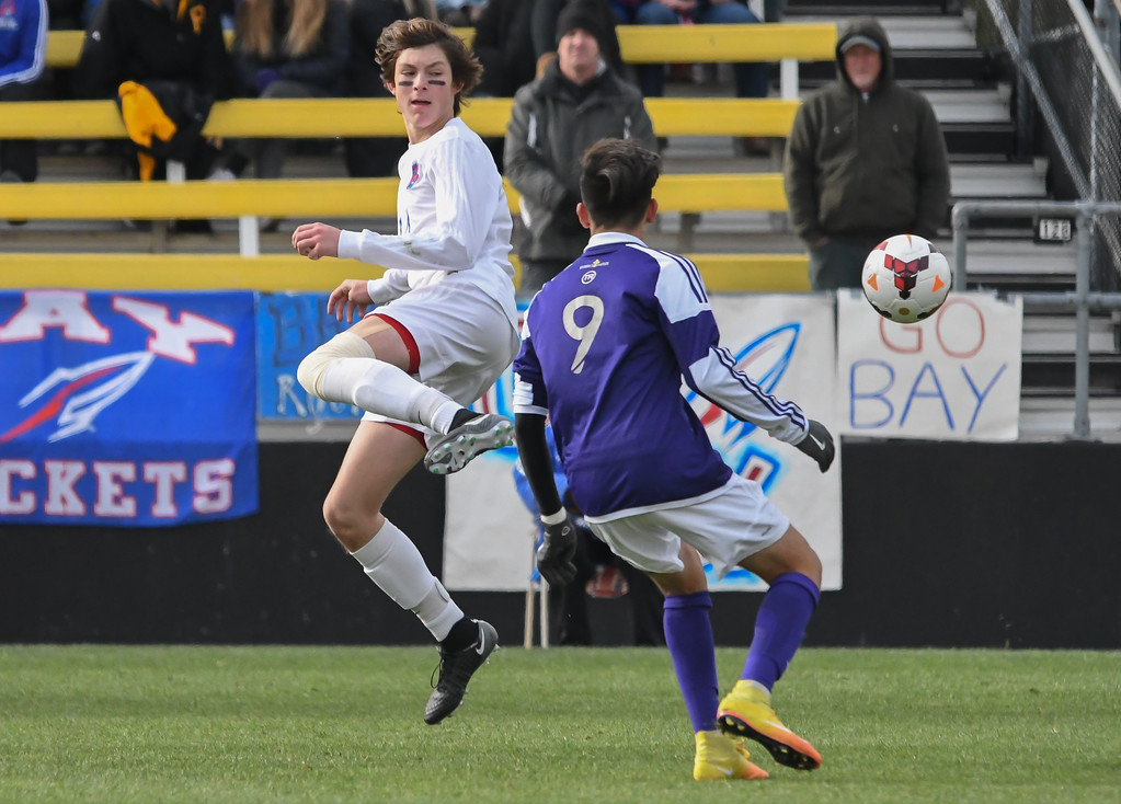 . Eric Bonzar�The Morning Journal<br> Bay forward Cade Gergye (14) clears the ball past Columbus St. Francis DeSales\' midfielder Cristian Gomez (9) in the D-II State Soccer Championship game, Nov. 11, 2017.