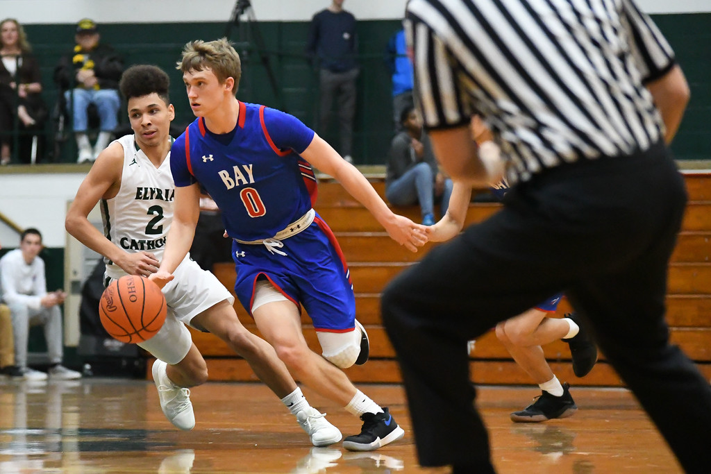 . Eric Bonzar�The Morning Journal<br> Bay\'s Erik Painter dribbles the ball past half court as he\'s defended by Elyria Catholic guard Donovan Warfield.