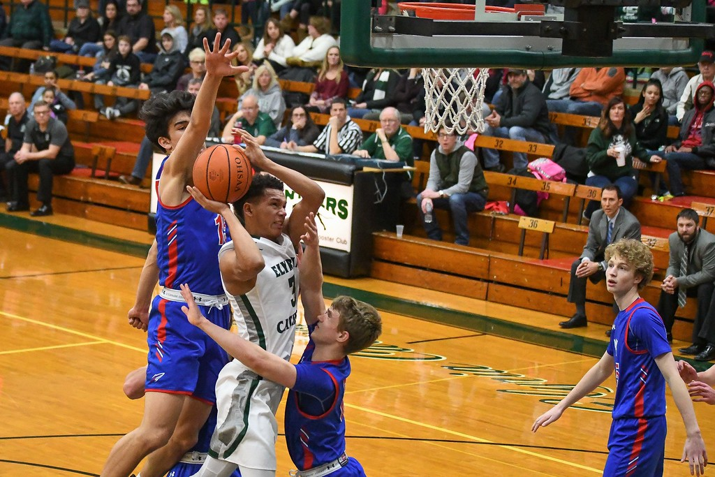 . Eric Bonzar�The Morning Journal<br> Elyria Catholic\'s Dorian Crutcher is sandwiched between Bay guards RJ Sunahara (15) and Erik Painter on his way to the rim.