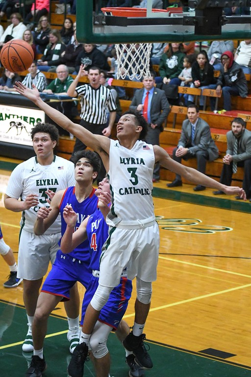 . Eric Bonzar�The Morning Journal<br> Elyria Catholic guard Dorian Crutcher stretches out for an offensive rebound.