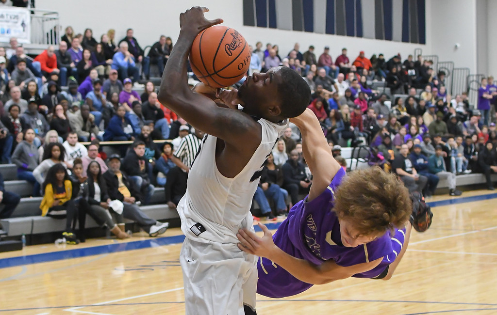 . Eric Bonzar�The Morning Journal Lorain forward Naz Bohannon (33) is fouled under the hoop by Vermilion\'s Jonah Pfeil (42).