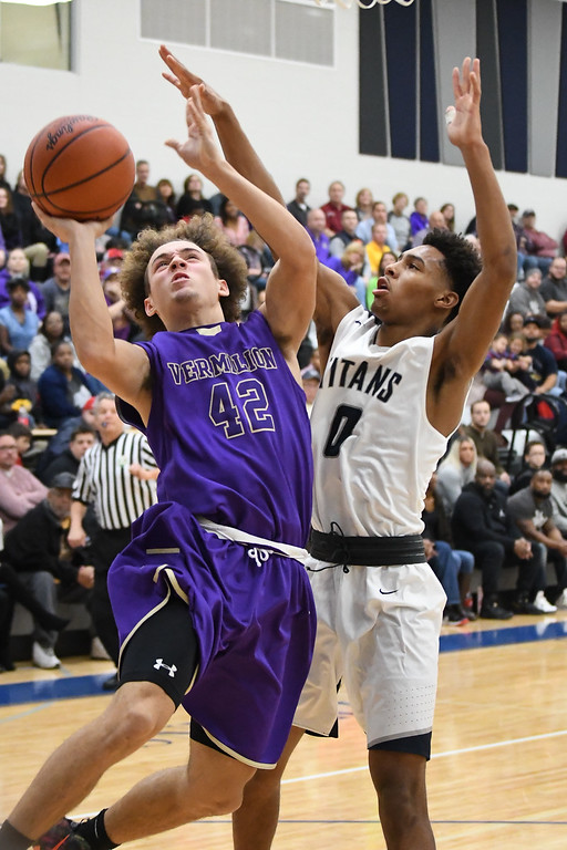 . Eric Bonzar�The Morning Journal Vermilion\'s Jonah Pfeil (42) shoots around the defense of Lorain guard Devone Grant (0).