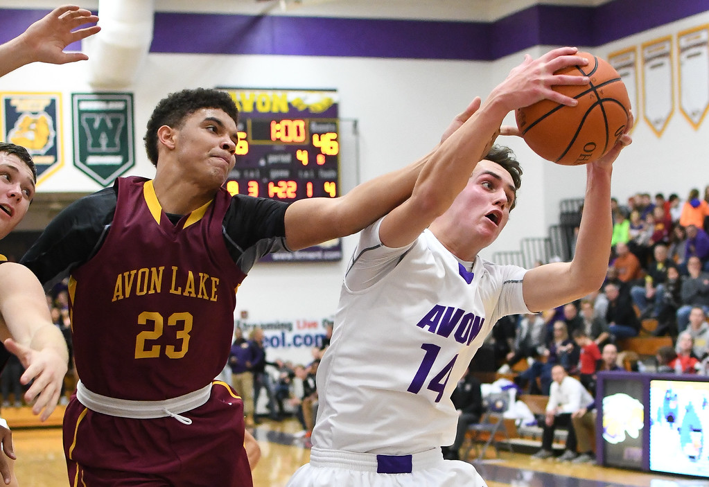 . Eric Bonzar�The Morning Journal Avon\'s Justin Ladegaard (14) snags a rebound over Avon Lake\'s Barris Coleman (23). Ladegaard had a game high nine boards in the Eagles\' 52-46 win over the Shoremen, Dec. 9, 2016.
