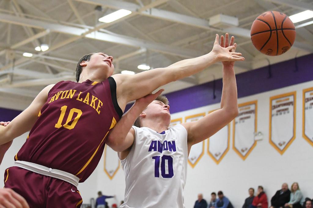 . Eric Bonzar�The Morning Journal Avon Lake\'s David Marsh (10) and Avon\'s Jacob Chasteen (10) fight for a rebound under the rim.