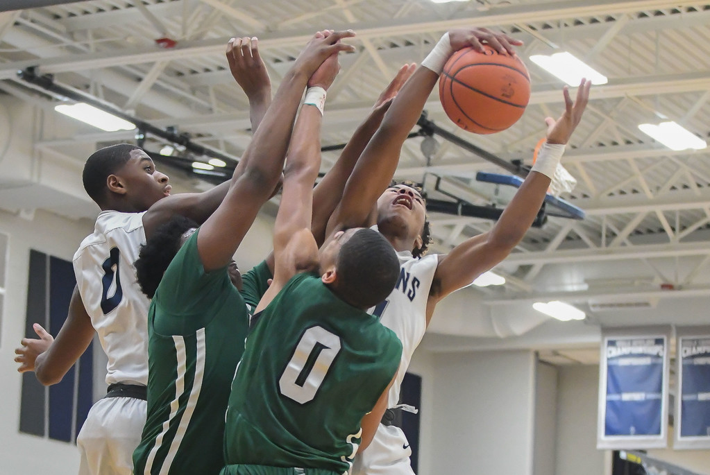 . Eric Bonzar�The Morning Journal<br> Lorain guard Jordan Jackson snags a rebound over Bedford defenders Carlos Hall (0) and Anthony Lett, Dec. 15, 2017.