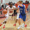 Eric Bonzar—The Morning Journal<br /> Elyria's Antonio Blanton (22) drives past Brunswick's Kyle Goessler (1), Dec. 16, 2016.