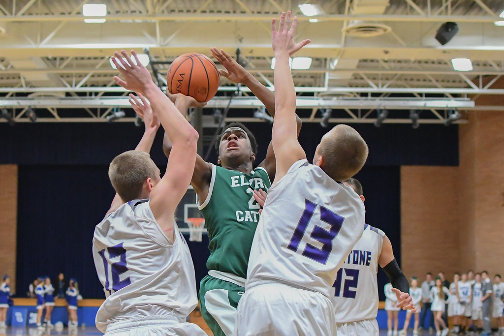 . Eric Bonzar�The Morning Journal Elyria Catholic\'s Doug Taylor Jr. (22) shoots over the Keystone defense of Kevin Mealwitz (12) and Matt Mealwitz (13).