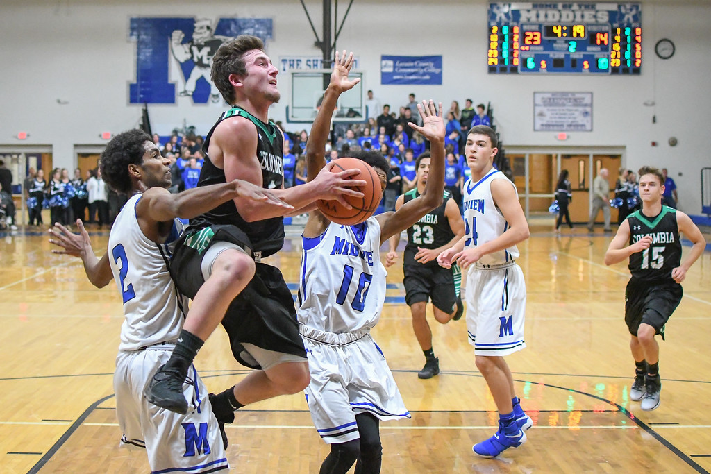 . Eric Bonzar�The Morning Journal Columbia\'s Austin Sahlica (1) is fouled on his way to the rim by Midview\'s Keith Johnson (2).