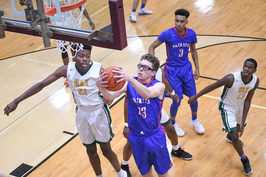 . Eric Bonzar�The Morning Journal<br> Open Door\'s Maxx Wiley snags an offensive rebound over John Hay\'s Sherman Kyle (21).