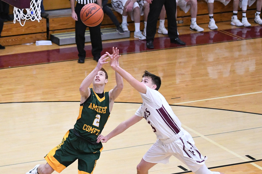 . Eric Bonzar�The Morning Journal<br> Amherst\'s Troy Toth and Wellington\'s Noah Diermyer fight for a rebound under the rim.