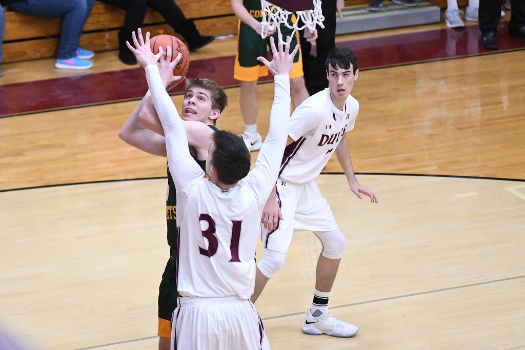 . Eric Bonzar�The Morning Journal<br> Amherst\'s Ryan Hritsko goes to the rim as he is defended by Wellington guard Colton Schmidt (31).