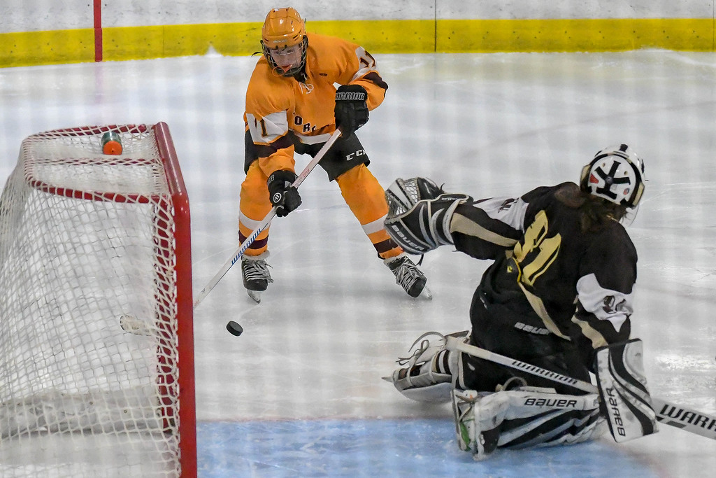 . Eric Bonzar�The Morning Journal Avon Lake forward Thomas Kacmarcik (11) tries to wrap the puck into the net around Brush goalie Mike Kornet.