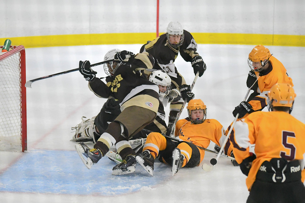 . Eric Bonzar�The Morning Journal Avon Lake forward Justin Share (14) tries to push the puck past a pair of Brush defenders and goalie Mike Kornet.