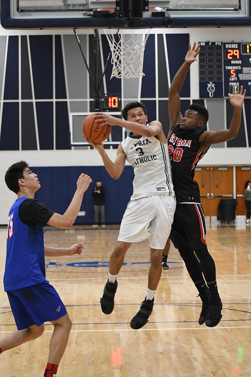 . Eric Bonzar�The Morning Journal Elyria Catholic\'s Dorian Crutcher is defended by Elyria\'s Deviian Williams and Bay\'s RJ Sunahara during the 3rd Coast Hoops Rising Stars game, April 15, 2017.
