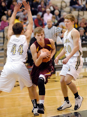 Alexandria's Braden Warren protects the ball as he drives through Lapel defenders Bobby Steele and Bailey Partington.