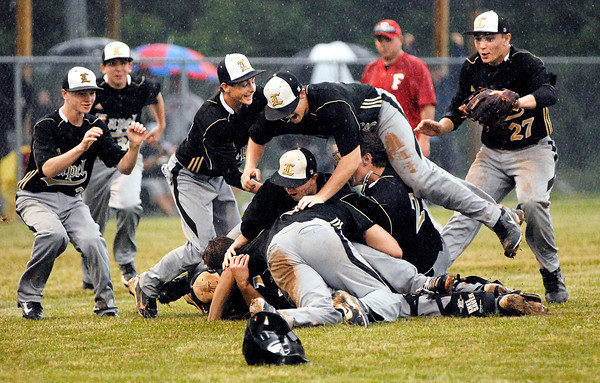 Lapel players start diving into the pile as they celebrate their 6 to 3 victory over Frankton in the 2A Lapel Baseball Sectional Monday.
